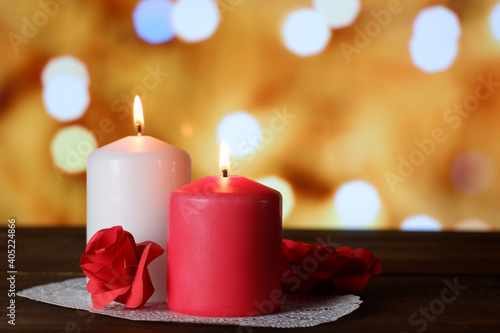 White and pink burning aromatic candles and roses on white openwork paper napkin on wooden table, yellow bokeh lights background selective focus. Love, Valentine's, women's day, romantic concept