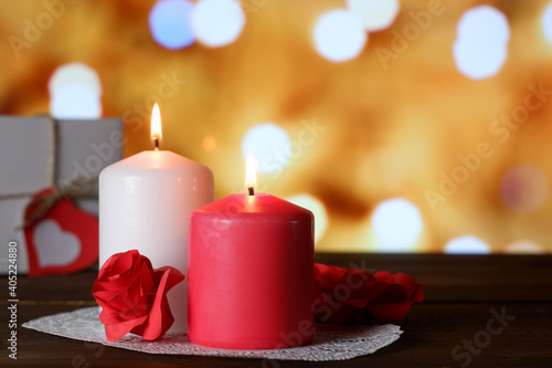 White and pink burning aromatic candles, roses, gift on white openwork paper napkin on wooden table, yellow bokeh lights background selective focus. Love, Valentine's, women's day, romantic concept