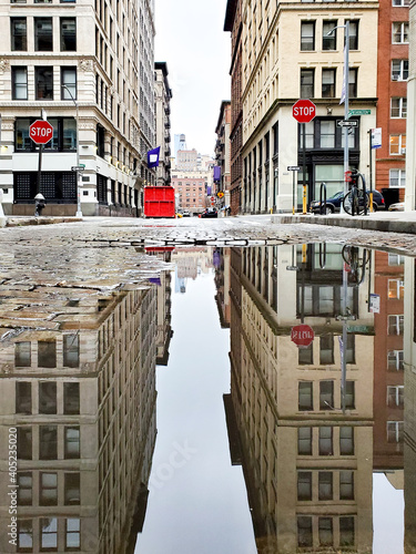 Fotografie, Obraz Buildings reflected in a puddle on Green Street in New York City