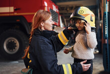 Happy Little Girl Is With Female Firefighter In Protective Uniform