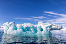 Blue Ice Iceberg, Formed When A Glacier Calves, Floating In The Arctic Waters Of Svalbard, Arctic Circle
