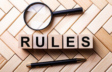 Wooden Cubes With The Word RULES Stand On A Wooden Background Between A Magnifying Glass And A Pen