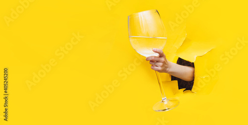 Fototapeta A left woman's hand emerges through a torn hole in yellow paper with a large glass with vermouth, water or vodka