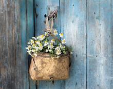 A Bunch Of Daisies In An Old Basket Hangs On The Door Handle.