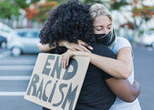 Young African Woman Hugging A Caucasian Woman After A Protest - Northern Woman With End Racism Bannner In Her Hands - Concept Of No Racism