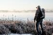 Samotny mężczyzna na brzegu jeziora zimą