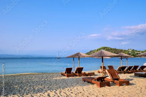 Fotografie, Obraz Aegean sea, sun loungers, and umbrellas at the Koukounaries beach in Skiathos is