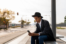 Young Man In Hat Using Smart Phone At Bus Stop On Sunny Day