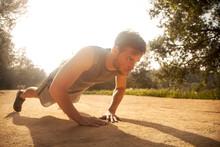 Athlete Exercising While Doing Push-ups On Footpath