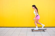 Beautiful Girl Skateboarding Along Yellow Wall In Summer