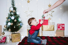 Mother Giving Bauble To Baby Boy Sitting On Blanket At Home During Christmas