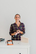 Smiling Woman Changing Drill Bit While Standing At Home