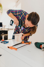 Woman Doing Fitting Screw With Electric Screwdriver While Working At Home