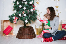 Smiling Mother And Son Playing With Bauble On Christmas Tree While Sitting At Home