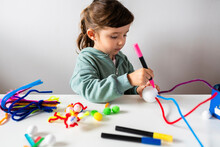 Cute Girl Making Creative Toys From Pipe Cleaners And Styrofoam Ball At Table