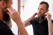 Mid Adult Man Brushing Beard With Comb While Looking At Mirror In Living Room