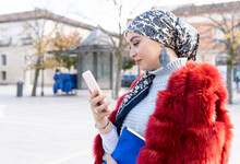 Smiling Woman Wearing Headscarf And Fur Coat Using Mobile Phone While Standing In City