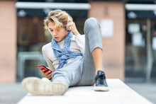 Young Man Wearing Headphones Using Mobile Phone While Relaxing On Bench In City
