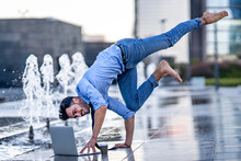Businessman Using Laptop While Doing Handstand On Footpath By Fountain