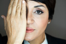 Portrait Of Businesswoman Covering Face With Hand