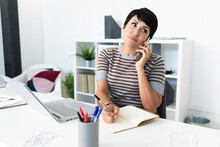 Portrait Of Businesswoman Talking On Smart Phone At Office Desk