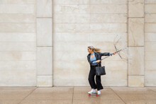 Cheerful Female Professional Skateboarding While Holding Damaged Umbrella Against Wall On Rainy Day
