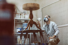 Carpenter With Protective Face Mask Lacquering Table While Working At Workshop