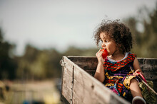 Girl Eating Tomato While Sitting In Truck