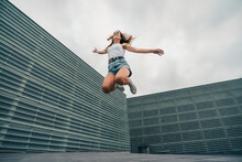 Carefree Young Woman Jumping With Arms Outstretched Against Sky