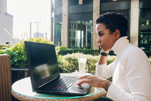 Businesswoman Working On Laptop At Cafe On Sunny Day