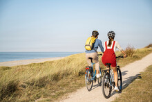Young Couple Wearing Cycling Helmet Riding Bicycles Against Clear Sky