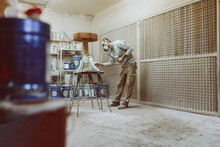 Manual Worker Painting Table With Spray Gun While Standing At Workshop