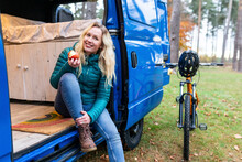 Smiling Woman Having Apple While Sitting At Door Of Camper Van At Cannock Chase