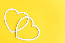 Two Hearts Made Of White Cardboard On A Yellow Background With Space For Text. Postcard Layout For The Holiday.