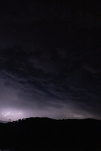 Strong Lightning In And Behind Big Towering Thunderclouds