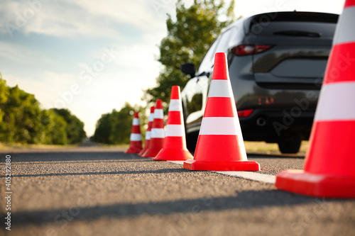 Billede på lærred Traffic cones near car outdoors. Driving school exam