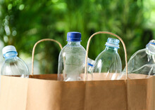 Paper Bag With Used Plastic Bottles Against Blurred Background, Closeup. Recycle Concept