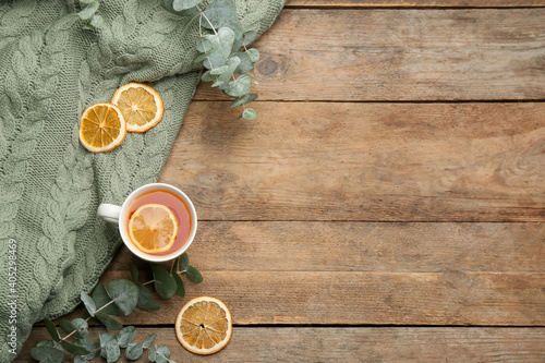 Flat lay composition with tea and warm plaid on wooden table, space for text
