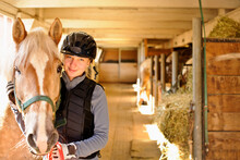 Portrait Of Teenage Girl (16-17) With Horse In Stable