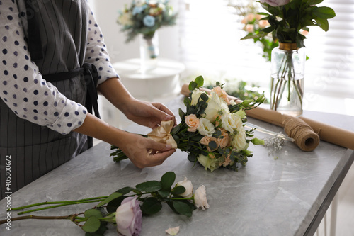 Obraz na plátně Florist tieing bow of beautiful wedding bouquet at light grey marble table, clos
