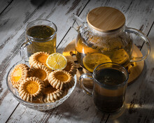 Glass Teapot With Herbal Lemon Tea, Two Cups Of Tea And Glass Bowl With Honey Cookies, Top View Still Life