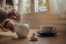 Senior Woman's Hands Preparing Tea In Kettle On Kitchen Table
