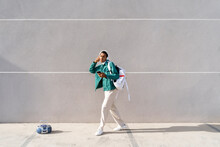 Young Man With Headphones And Mobile Phone Carrying Bag While Dancing No Footpath