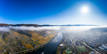 Germany, Rhineland-Palatinate, Bernkastel-Kues, Helicopter View Of Riverside Town And Hillside Vineyards At Foggy Autumn Morning