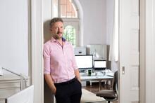 Elegant Businessman Leaning On Doorway Of Office Cabin