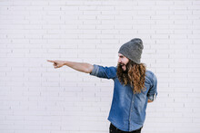 Happy Young Man In Knit Hat Pointing While Standing Against Brick Wall