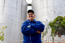 Smiling Male Winemaker With Arms Crossed At Winery Factory