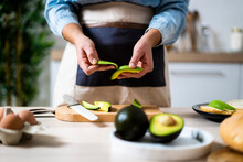 Mid Section Of Woman Peeling Avocados