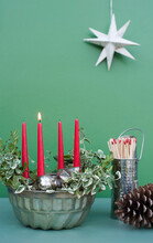 Studio Shot Of DIY Advent Decorations Including Candles, Twigs, Pine Cone, Matches And Baking Pan