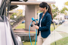 Businesswoman Holding Electric Car Charger At Station